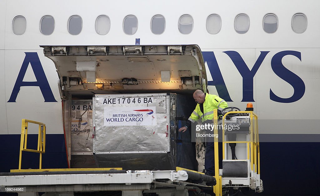 An employee removes a cargo container from the hold of a British Airways aircraft at Gatwick airport in Crawley, U.K., on Thursday, Jan. 10, 2013. Gatwick, acquired by Global Infrastructure Partners Ltd. in 2009 after regulators sought a breakup of BAA Ltd., owner of the larger Heathrow hub, is 30 miles (48 kilometers) south of London and serves about 200 destinations, more than any other U.K. airport, according to flight schedule data provider OAG. Photographer: Chris Ratcliffe/Bloomberg via Getty Images