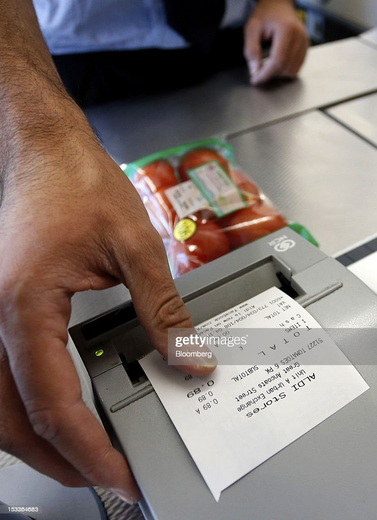 An employee removes a receipt from a cash register at a supermarket operated by Aldi Group, Germany's biggest discount-food retailer, in Manchester, U.K., on Thursday, Oct. 4, 2012. U.K. shop-price inflation slowed in September as retailers offered discounts to attract cash-strapped consumers, the British Retail Consortium said. Photographer: Paul Thomas/Bloomberg via Getty Images