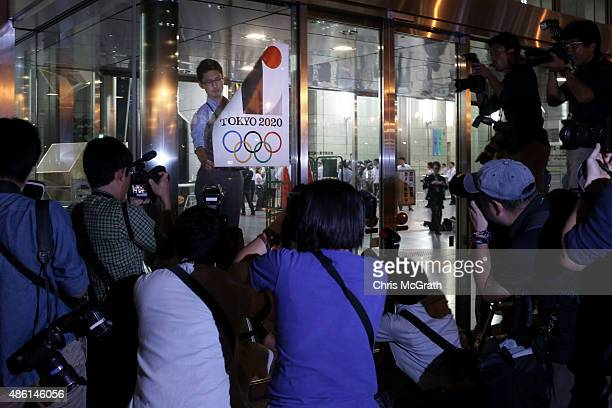 An employee removes a Tokyo 2020 Olympic poster showing the copied logo design hung at the entrance of the Tokyo Metropolitan Government Office...