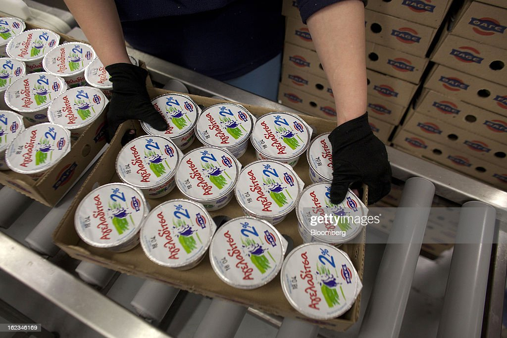 An employee removes a tray of Greek yoghurt from a conveyor belt during manufacture at the Fage Dairy Industry SA plant in Athens, Greece, on Thursday, Feb. 21, 2013. An October restructuring that placed Fage International SA's Greek units in a subsidiary called Fage Dairy Industry SA coincided with Coca-Cola Hellenic Bottling SA's plan to flee the epicenter of Europe's debt crisis by moving its main stock listing to London from Athens. Photographer: Kostas Tsironis/Bloomberg via Getty Images