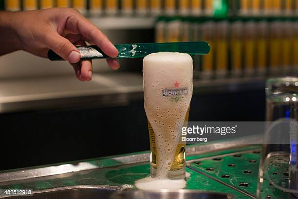 An employee removes excess foam from the top of a glass of draught Heineken lager beer in the Heineken NV Experience bar in Amsterdam Netherlands on...