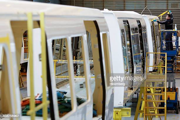An employee removes protective tape from the window aperture of a Copenhagen metro train carriage during manufacture at AnsaldoBreda SpA's rail car...