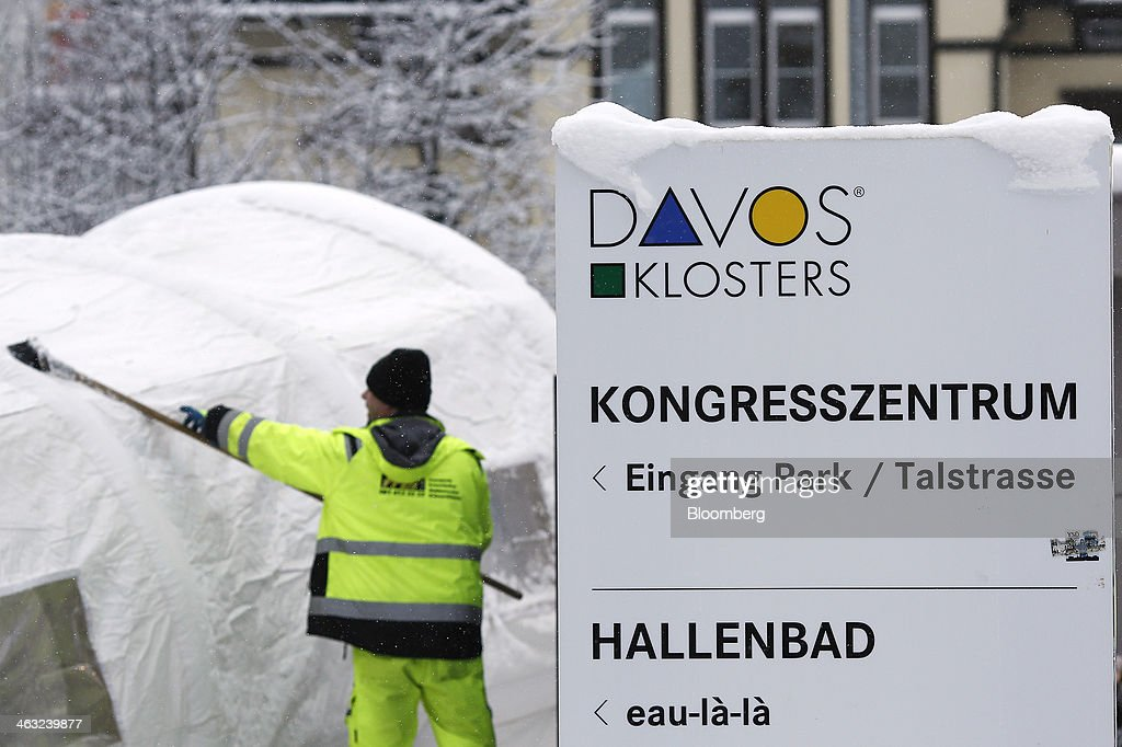 An employee removes snow from the roof of an entrance into the Kongress Zentrum, or Congress Center, the venue for the World Economic Forum (WEF) in Davos, Switzerland, on Friday, Jan. 17, 2014. Next week the business elite will gather in the Swiss Alps for the 44th annual meeting of the World Economic Forum (WEF) in Davos for the five day event which runs from Jan. 22-25. Photographer: Simon Dawson/Bloomberg via Getty Images