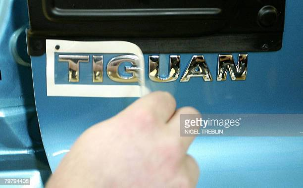 An employee removes tape from a Volkswagen Tiguan car at the company's plant in the northwestern German city of Wolfsburg February 15 2008 Volkswagen...