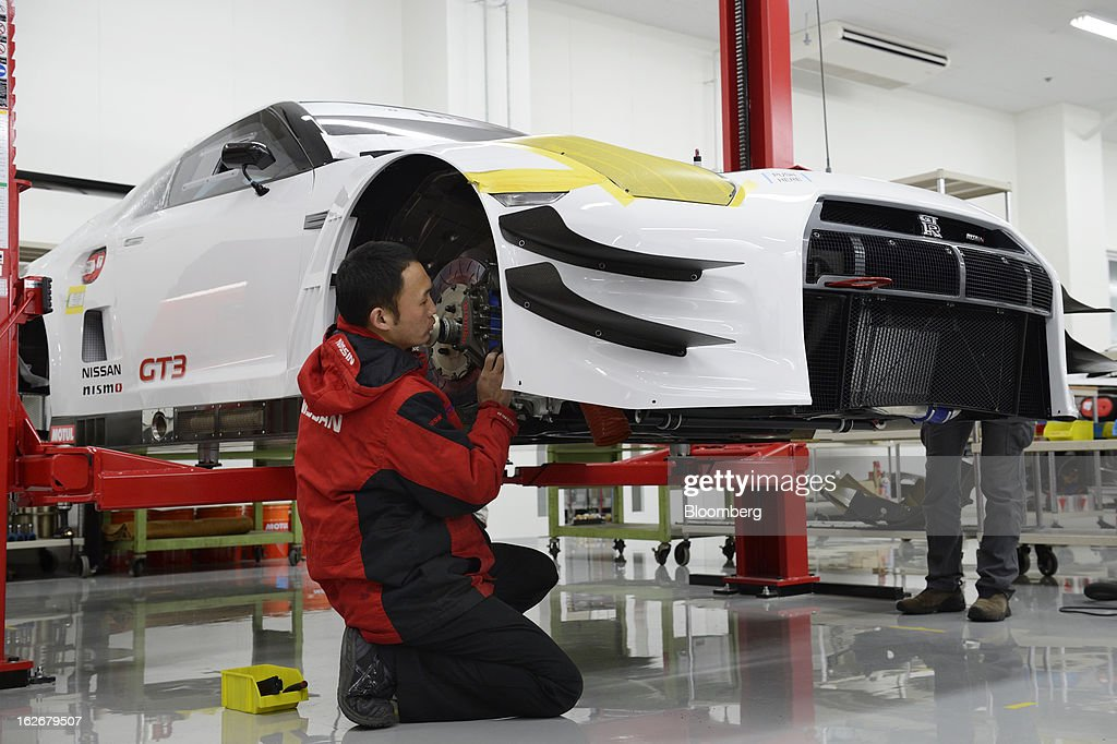 An employee repairs a Nissan Motor Co. GT-R Nismo vehicle in the repair shop at the Nismo global headquarters and development center in Yokohama City, Japan, on Tuesday, Feb. 26, 2013. Chief Executive Officer Carlos Ghosn, who has called 100 yen to the dollar the 'neutral' value for the Japanese currency, said the yen should weaken further. Photographer: Akio Kon/Bloomberg via Getty Images