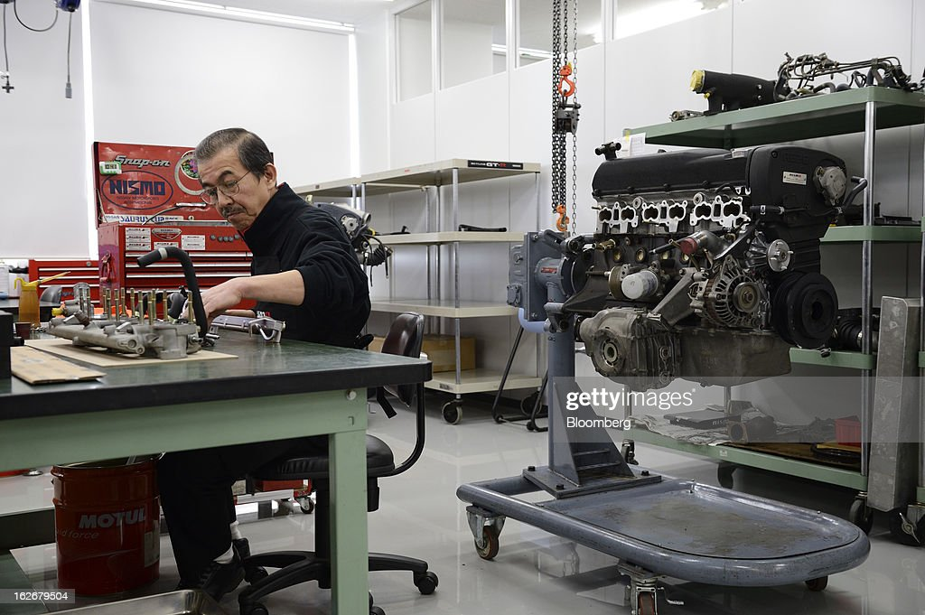 An employee repairs an engine for Nissan Motor Co. Nismo vehicles in the repair shop at the Nismo global headquarters and development center in Yokohama City, Japan, on Tuesday, Feb. 26, 2013. Chief Executive Officer Carlos Ghosn, who has called 100 yen to the dollar the 'neutral' value for the Japanese currency, said the yen should weaken further. Photographer: Akio Kon/Bloomberg via Getty Images