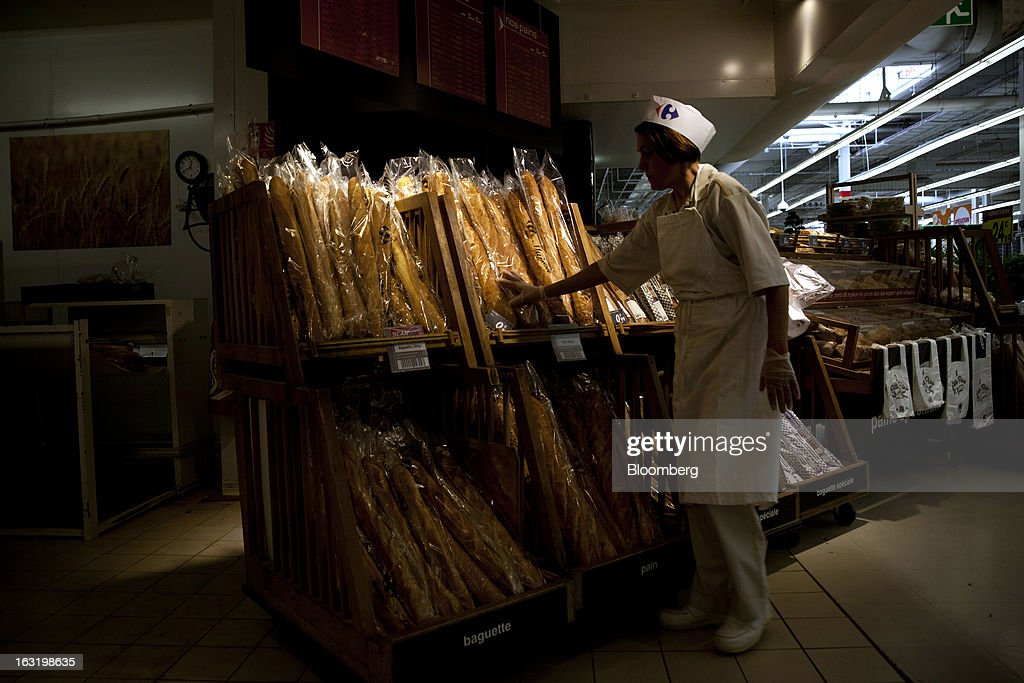 An employee re-stocks baguettes in the bakery department inside a Carrefour SA supermarket in Portet sur Garonne, near Toulouse, France, on Tuesday, March 5, 2013. Carrefour's stock has risen 47 percent since Georges Plassat's arrival as chief executive officer, partially offsetting a 71 percent decline in the preceding five years. Photographer: Balint Porneczi/Bloomberg via Getty Images
