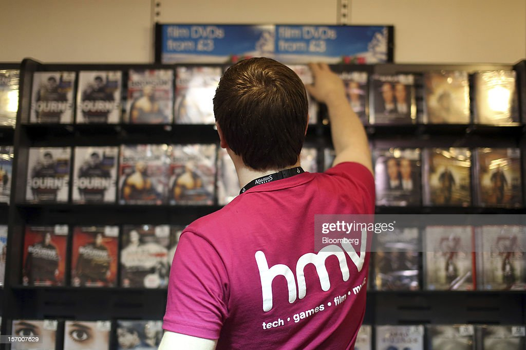 An employee re-stocks DVDs on to the display inside a HMV pop-up store, in this arranged photograph in London, U.K., on Tuesday, Nov. 27, 2012. Fashion chain Hobbs is among those that have opened pop-up stores for the first time this year, while CD and DVD retailer HMV Group Plc is adding more than usual for the holiday in an effort to win business. Photographer: Chris Ratcliffe/Bloomberg via Getty Images