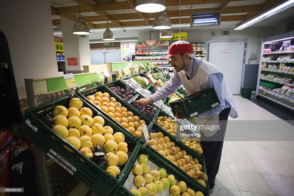 An employee re-stocks plums in the grocery section of an Eroski Group supermarket in Madrid, Spain, on Friday, Nov. 2, 2012. Spain is unlikely to need a full bailout while any request from the euro area's fourth-largest economy for alternative support measures must be met with a swift response, Finnish Prime Minister Jyrki Katainen said. Photographer: Angel Navarrete/Bloomberg via Getty Images