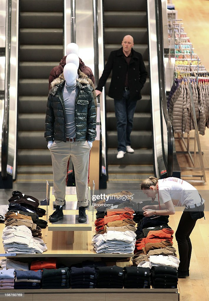 An employee, right, arranges a display of men's clothes inside Fast Retailing Co.'s Uniqlo store at the Westfield Stratford City shopping mall in London, U.K., on Thursday, Dec. 27, 2012. Overall Christmas shopping in the U.K. was similar to last year, according to the British Retail Consortium. Photographer: Chris Ratcliffe/Bloomberg via Getty Images