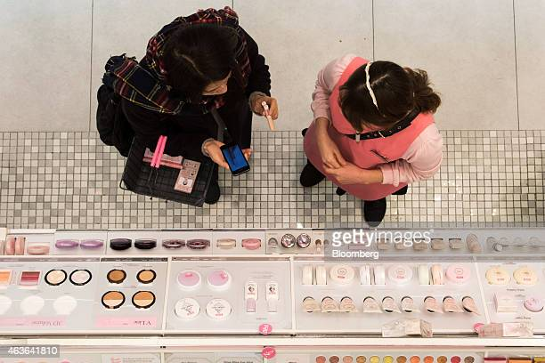 An employee right assists a Chinese tourist at an Amorepacific Corp Etude House store in the Myeongdong shopping district in Seoul South Korea on...