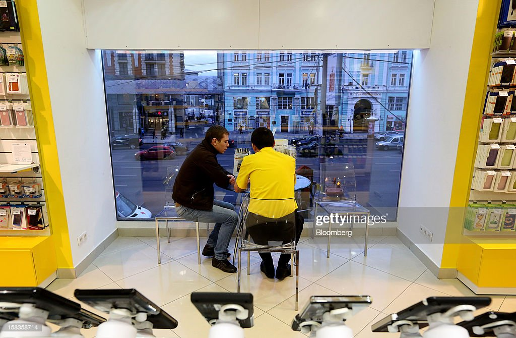 An employee, right, assists a customer in the window of a Euroset Holding NV mobile phone store in Moscow, Russia, on Thursday, Dec. 13, 2012. OAO MegaFon and its main shareholder billionaire Alisher Usmanov bought 50 percent of Euroset Holding NV in a deal that gives Russia's biggest handset retailer an enterprise value of $2.3 billion. Photographer: Andrey Rudakov/Bloomberg via Getty Images