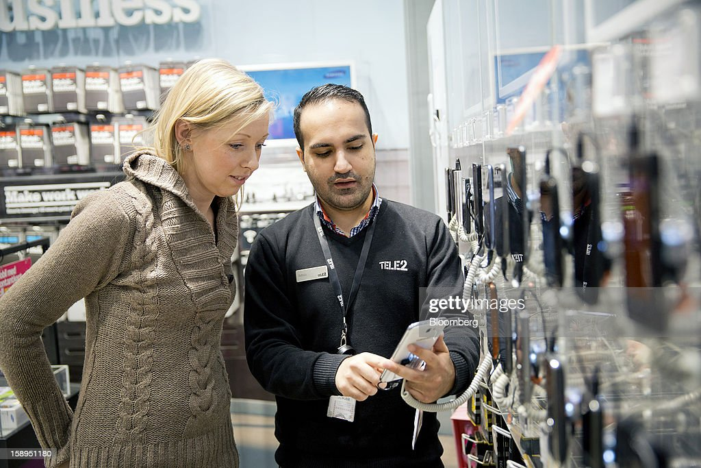 An employee, right, demonstrates a smartphone to a customer inside a Tele2 AB store at the Farsta Centrum shopping center in Stockholm, Sweden, on Friday, Jan. 4, 2013. OAO Rostelecom's largest owner after the Russian state, Konstantin Malofeev, is urging the country's dominant fixed-line operator to buy the local unit of Sweden's Tele2 AB to form a fourth nationwide wireless carrier. Photographer: Casper Hedberg/Bloomberg via Getty Images