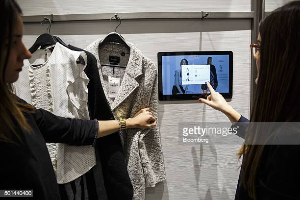 An employee right explains the function of a tablet computer to a customers in a changing booth at a Zara fashion store operated by Inditex SA in San...