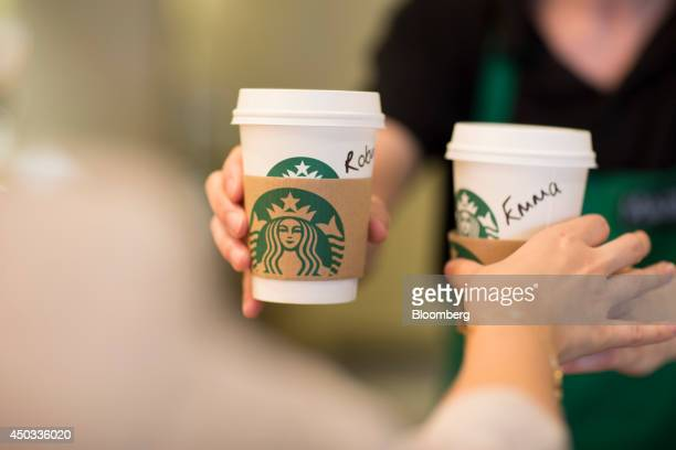 An employee right hands a customer personalised cardboard coffee cups inside a Starbucks Corp coffee shop in London UK on Monday June 9 2014 UK...