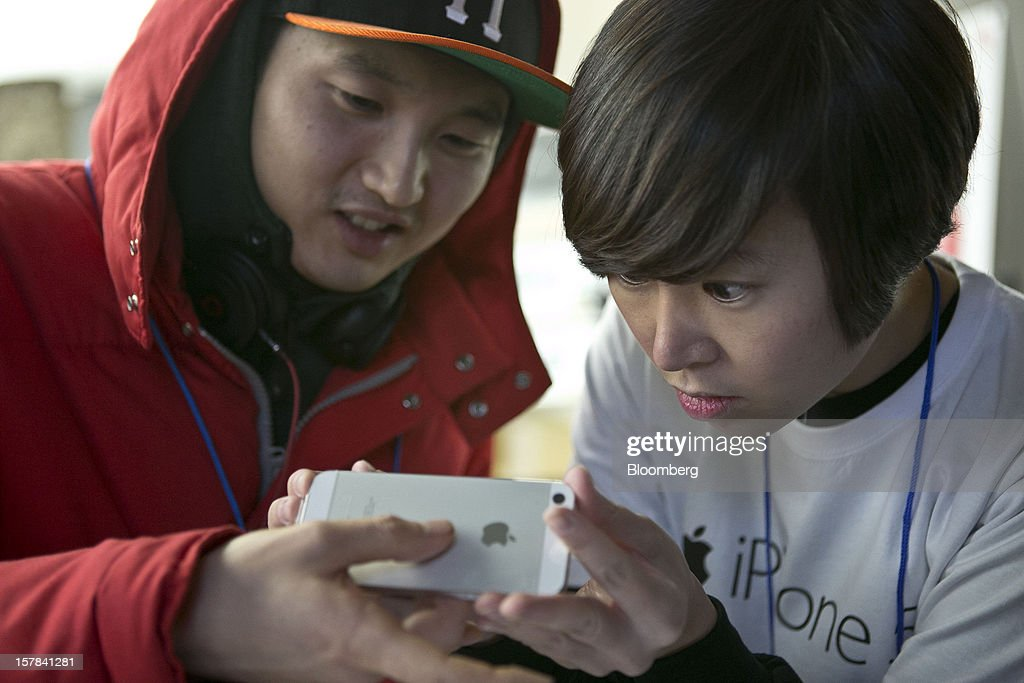 An employee, right, inspects an Apple Inc. iPhone 5 with customer Cho Min-woo, 32, at a KT Corp. Olleh brand mobile phone store in Seoul, South Korea, on Friday, Dec. 7, 2012. The iPhone 5 went on sale in South Korea today. Photographer: Jean Chung/Bloomberg via Getty Images