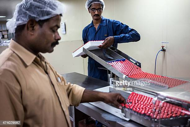 An employee right loads unlabeled vaccine vials into a machine in the labeling unit at the Serum Institute of India Ltd pharmaceutical plant in Pune...