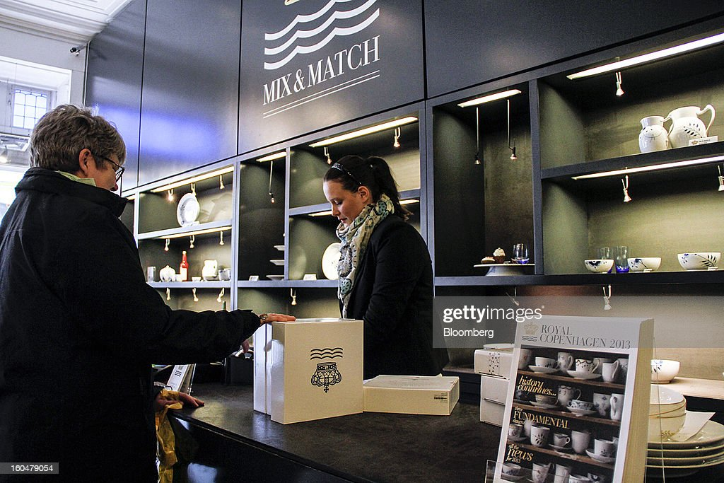 An employee, right, serves a customer with her purchases of Danish porcelain at the Royal Copenhagen store on Storget street in Copenhagen, Denmark, on Friday, Feb. 1, 2013. Danish regional banks are struggling to emerge from a burst property bubble that's forced the government resolution agency to take over a dozen lenders after losses on commercial and agricultural loans wiped out capital. Photographer: Freya Ingrid Morales/Bloomberg via Getty Images