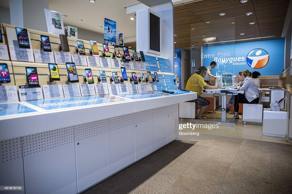 An employee, right, speaks with a customer as they sit inside a Bouygues Telecom store, operated by Bouygues SA in Paris, France, on Thursday, July 3, 2014. Bouygues Telecom, France's third-largest mobile operator, was looking for a buyer as profitability and cash generation declined. Photographer: Balint Porneczi/Bloomberg via Getty Images