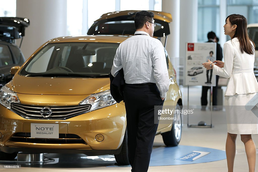 An employee, right, speaks with a customer as they walk past a Nissan Motor Co. Note Medalist vehicle displayed at the company's showroom in Yokohama, Kanagawa Prefecture, Japan, on Friday, Feb. 8, 2013. Nissan, Japan's second-biggest carmaker, reported third-quarter profit that fell short of analysts' estimates, after sales tumbled in China and new models trailed competitors in the U.S. Photographer: Kiyoshi Ota/Bloomberg via Getty Images