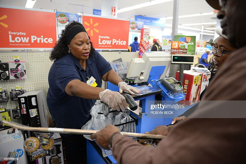 An employee rings up sales at a cash register at a Walmart in the Crenshaw district of Los Angeles on Black Friday November 29 2013 US stocks Friday...