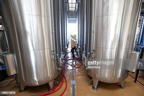 An employee samples some Prosecco wine from a fermenting tank at Cantina Sociale Cooperative Agricola di Vittorio Veneto winery in Conegliano Italy...