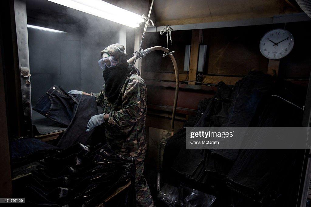 An employee sandblasts a pair of jeans at the Bitou denim processing facility in Kojima district on February 25 2014 in Kurashiki Japan Kojima is a...