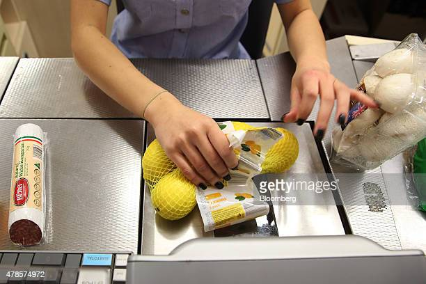 An employee scans a bag of lemons at the checkout counter of an Aldi Stores Ltd food store in Sydney Australia on Thursday June 25 2015 Australia's...