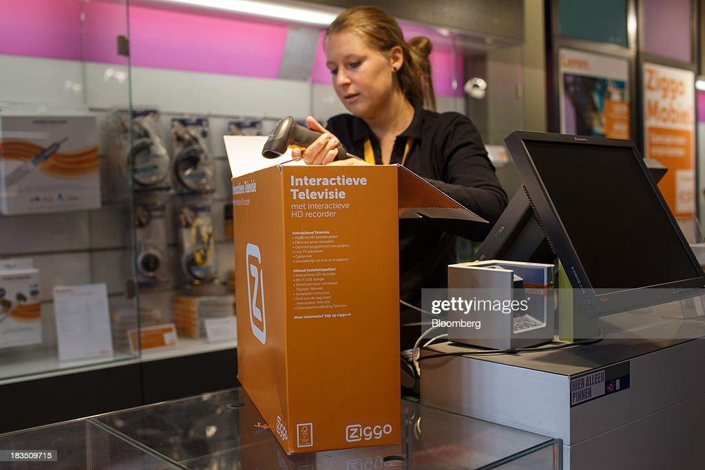 An employee scans a barcode on a Ziggo interactive high definition (HD) television recorder box inside a Ziggo NV store in Utrecht, Netherlands, on Friday, Oct. 4, 2013. Cable-TV provider Ziggo, which is 28.5 percent owned by Liberty Global Plc, is pushing into the Dutch mobile market with low-priced packages, following a playbook pioneered by French discount operator Iliad SA. Photographer: Jasper Juinen/Bloomberg via Getty Images