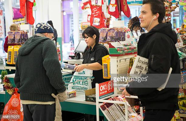 An employee scans a customers goods at a checkout desk inside a Poundland discount store operated by Poundland Holdings Ltd in Birmingham UK on...
