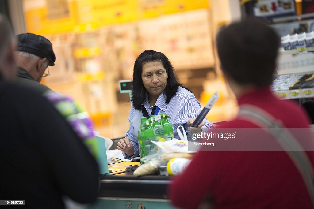 An employee scans a customer's products at a checkout desk inside a Carrefour SA supermarket at the Mall of Cyprus in Nicosia, Cyprus, on Tuesday, March 26, 2013. Controls on capital movements to prevent money from draining out of the banking system -- allowed in exceptional circumstances under European Union law -- will remain for 'a matter of weeks,' Cypriot Finance Minister Michael Sarris said. Photographer: Simon Dawson/Bloomberg via Getty Images