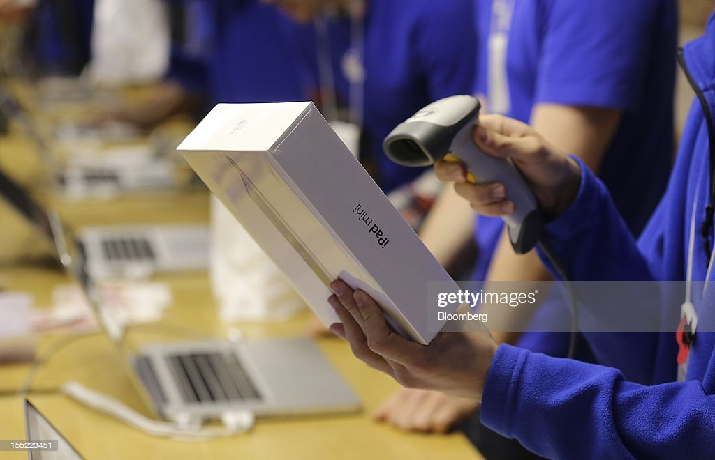 An employee scans a customer's purchase of an Apple Inc. iPad mini at the company's Covent Garden store in London, U.K., on Friday, Nov. 2, 2012. Apple Inc.'s iPad mini tablet goes on sale in the U.K. today. Photographer: Simon Dawson/Bloomberg via Getty Images