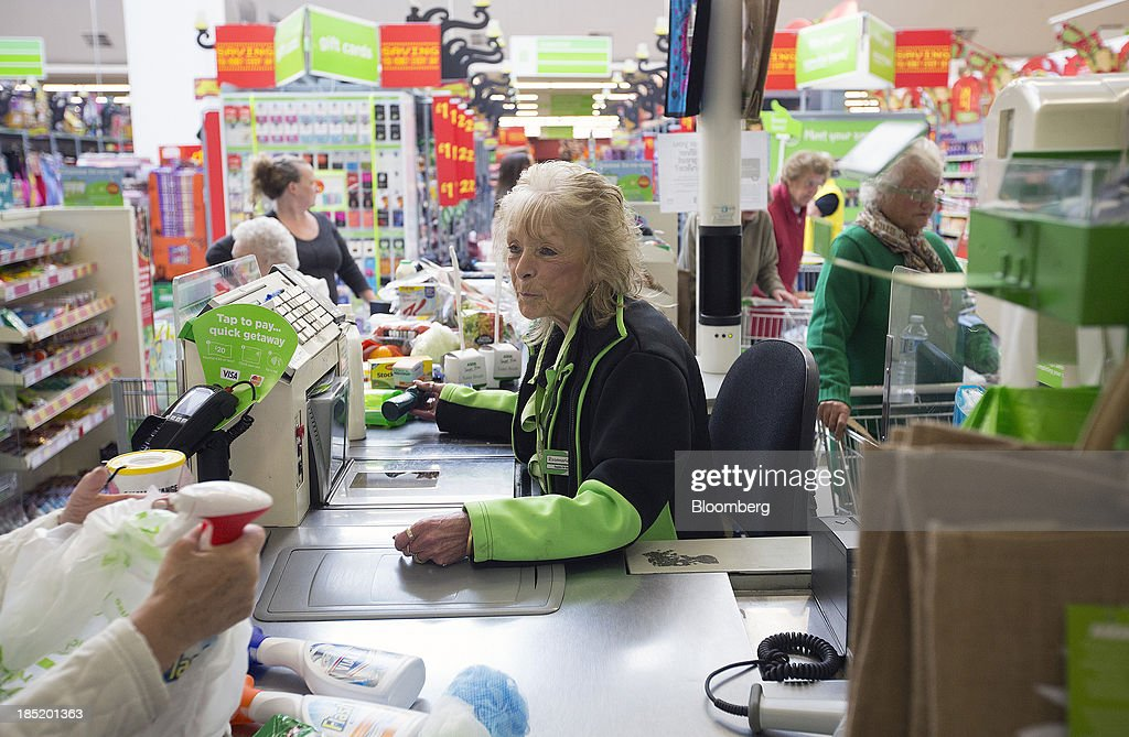 An employee scans a customer's purchases through a till at a checkout desk inside an Asda supermarket the UK retail arm of WalMart Stores Inc in...