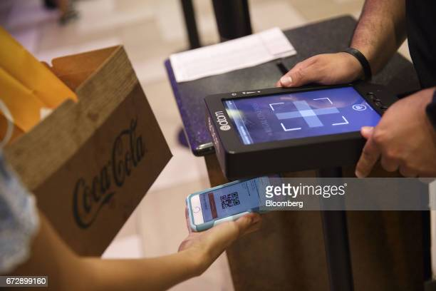 An employee scans a mobile ticket QR code displayed on an Apple Inc iPhone at the Regal Cinemas LA LIVE Stadium 14 movie theater in Los Angeles...