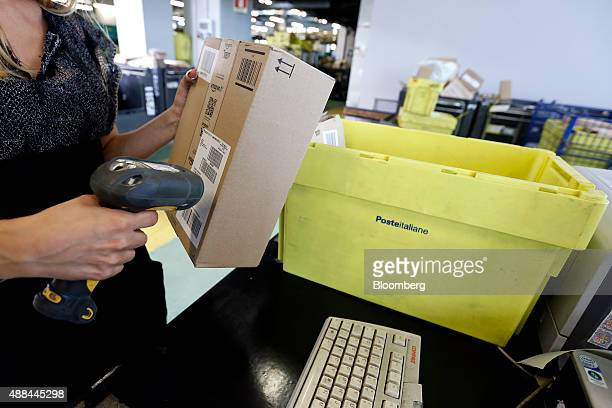 An employee scans a package inside a Poste Italiane SpA postal sorting office in Fiumicino near Rome Italy on Tuesday Sept 15 2015 Italy is...