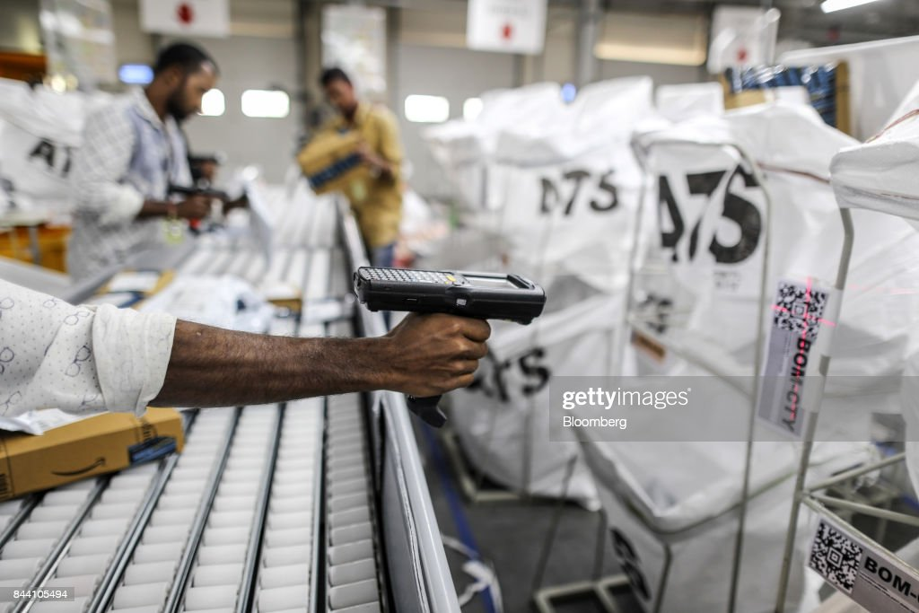 An employee scans a QR code while preparing package for shipping at the Amazon.com Inc. fulfillment center in Hyderabad, India on Thursday, Sept. 7, 2017. Amazon opened its largest Indian fulfillment center in Hyderabad. The center spans 400,000 square feet with 2.1m cubic feet of storage capacity the company said in a statement. Photographer: Dhiraj Singh/Bloomberg via Getty Images