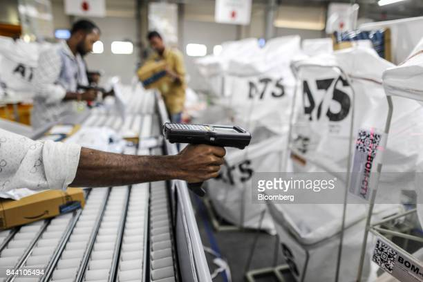 An employee scans a QR code while preparing package for shipping at the Amazoncom Inc fulfillment center in Hyderabad India on Thursday Sept 7 2017...