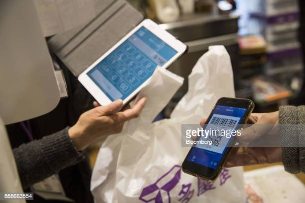 An employee scans a quick response code displayed on the Ant Financial Services Group's Alipay app an affiliate of Alibaba Group Holding Ltd at a...
