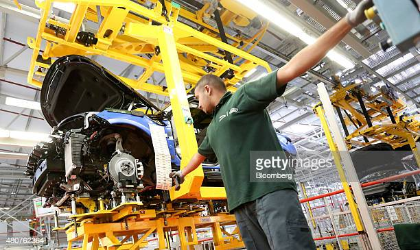 An employee scans an identification label on a Range Rover Sport SUV as it moves along the production line at Tata Motors Ltd's Jaguar Land Rover...