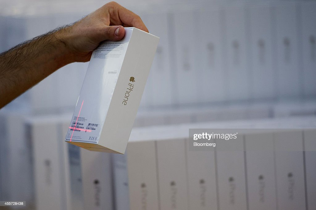 An employee scans an iPhone 6 during the sales launch at the Apple Inc. store in Palo Alto, California, U.S., on Friday, Sept. 19, 2014. Apple Inc.'s stores attracted long lines of shoppers for the debut of the latest iPhones, indicating healthy demand for the bigger-screen smartphones. The larger iPhone 6 Plus is already selling out at some stores across the U.S. Photographer: David Paul Morris/Bloomberg via Getty Images