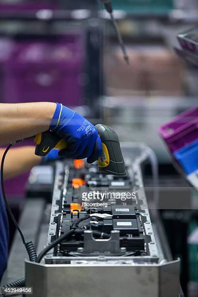 An employee scans barcodes on lithiumion battery components at the Bayerische Motoren Werke AG automobile manufacturing plant in Dingolfing Germany...