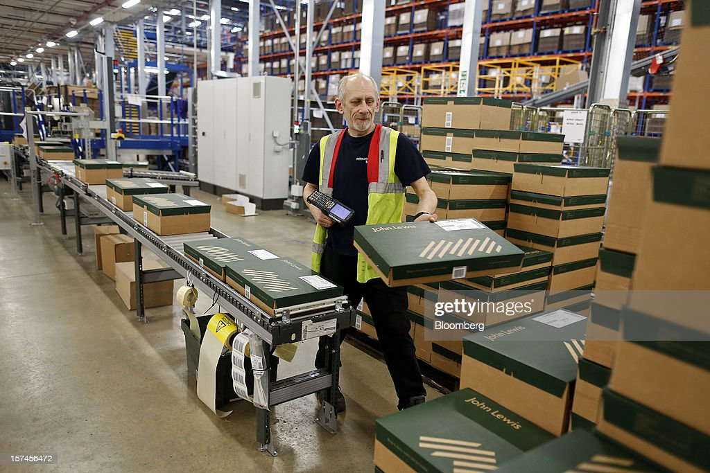 An employee scans customers' goods in cardboard boxes as they are prepared for dispatch at the John Lewis Plc distribution centre in Milton Keynes, U.K., on Monday, Dec. 3, 2012. An index of U.K. retail sales rose to a five-month high in November, according to a monthly report from the Confederation of British Industry. Photographer: Simon Dawson/Bloomberg via Getty Images
