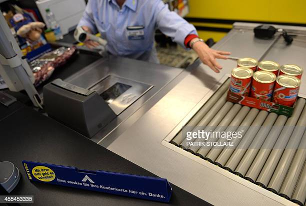An employee scans goods through at cash register at the retail and wholesale/cash and carry group Metro supermarket in Cologne Germany on December 12...