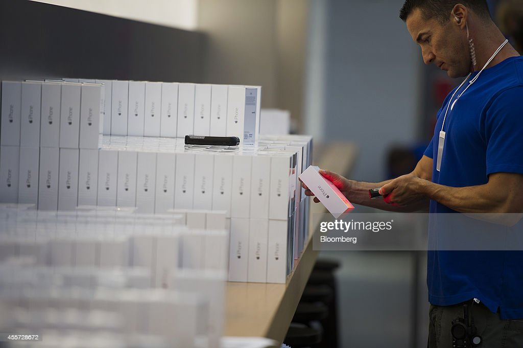 An employee scans iPhone 6 boxes during the sales launch at the Apple Inc. store in Palo Alto, California, U.S., on Friday, Sept. 19, 2014. Apple Inc.'s stores attracted long lines of shoppers for the debut of the latest iPhones, indicating healthy demand for the bigger-screen smartphones. The larger iPhone 6 Plus is already selling out at some stores across the U.S. Photographer: David Paul Morris/Bloomberg via Getty Images