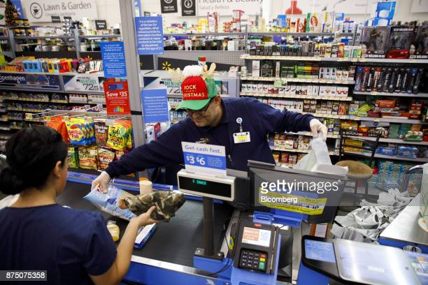 An employee scans items for a customer at a WalMart Stores Inc location in Burbank California US on Thursday Nov 16 2017 Black Friday the day after...
