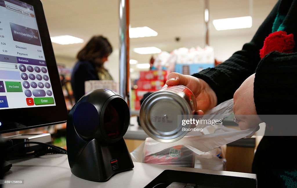 An employee scans the barcode on a tin of food at the check-out desk inside the Community shop, a supermarket for low-income families, in Goldthorpe, U.K., on Monday, Dec. 23, 2013. Company Shop Ltd. created the Community shop for people in, or bordering on, food poverty, selling surplus goods from major retailers at discounted prices. Photographer: Paul Thomas/Bloomberg via Getty Images