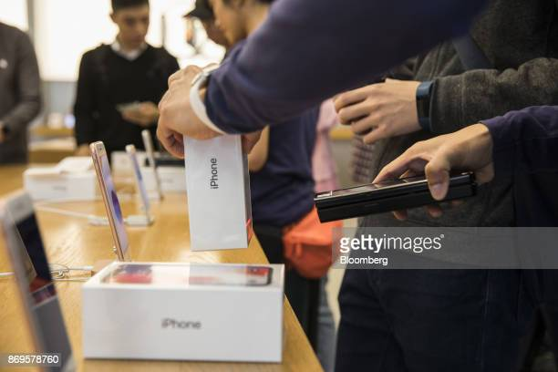 An employee scans the barcode on the box of an Apple Inc iPhone X at an Apple store during its launch in Hong Kong China on Friday Nov 3 2017 Long...