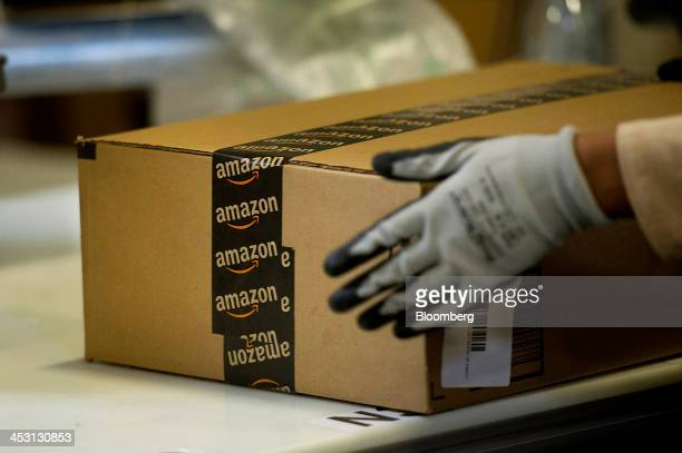 An employee seals a box at the Amazoncom Inc fulfillment center in Phoenix Arizona US on Monday Dec 2 2013 More than 131 million consumers are...