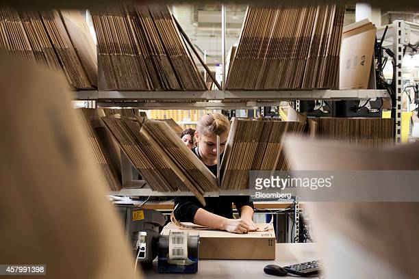 An employee seals a cardboard box with packing tape ahead of shipping at the new Amazon Inc fulfilment center on its official day of opening in...