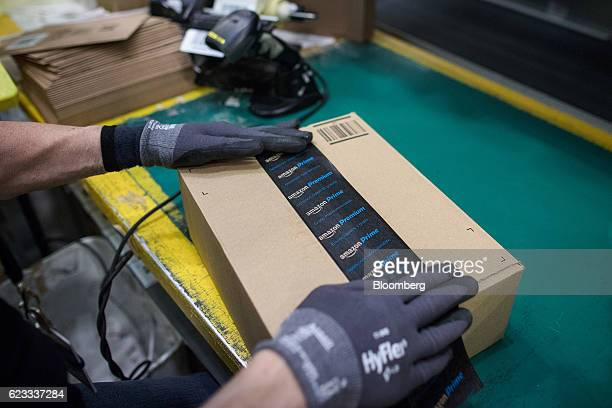 An employee seals a delivery box with tape with Amazon Prime and Amazon Premium branding at an Amazoncom Inc fulfillment center in Peterborough UK on...